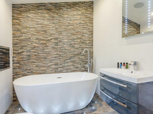 Family bathroom with large freestanding bath and TV built in to the wall