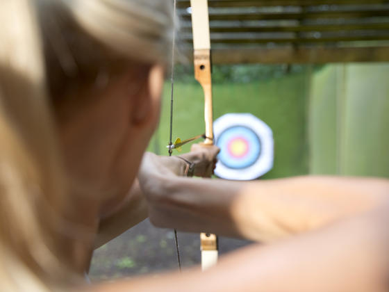 Lady with bow & arrow shooting at an archery target