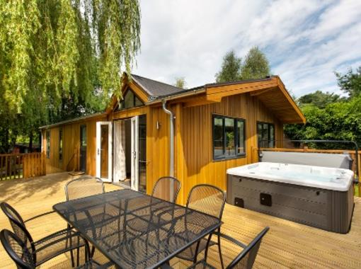 Modern pine lodge with dining furniture and outdoor hot tub on the verandah with willow tree