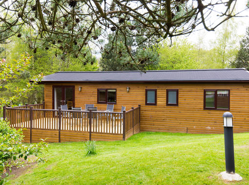 Exterior of lodge with decking to the side with outdoor furniture