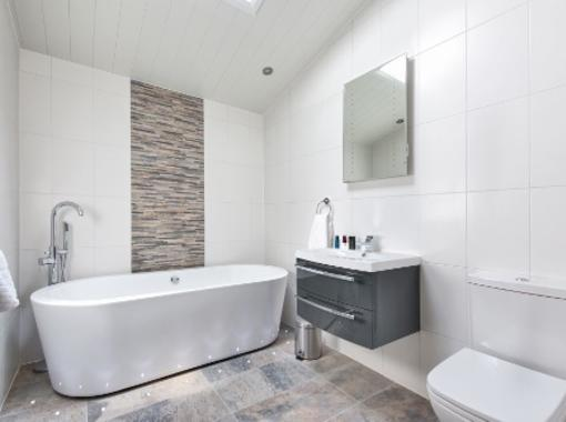 Modern bathroom with large freestanding bath and feature tile wall