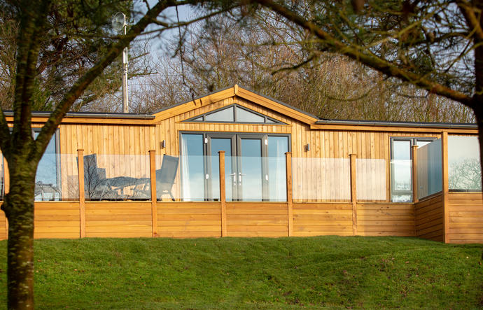 Modern and stylish lodge with glass screening to the decking area