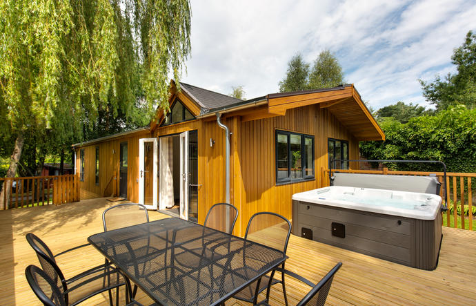 Exterior of Willow spa lodge with outdoor hot tub and outdoor dining furniture and willow tree to the side of the lodge